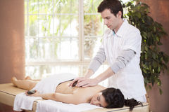 Therapist giving a stone massage Royalty Free Stock Image