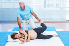 Therapist giving treatment to pregnant woman lying on mattress Royalty Free Stock Images