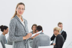 Therapist with group therapy in session in background. Portrait of a serious female therapist with group therapy in session in background Stock Photo