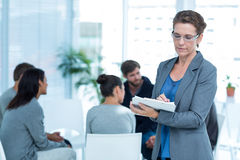 Therapist with group therapy in session. Portrait of a smiling female therapist with group therapy in session in background royalty free stock images