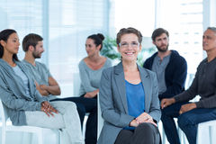 Therapist with group therapy in session. Portrait of a smiling female therapist with group therapy in session in background royalty free stock photo