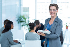 Therapist with group therapy in session. Portrait of a smiling female therapist with group therapy in session in background Stock Images