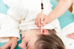 Free Therapist Hand With Burning Ear Candle In Woman`s Ear Stock Photo - 128352120