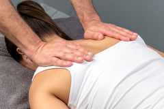 Therapist hands applying pressure on female shoulder blades. royalty free stock images