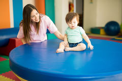 Therapist helping a baby practice balance. Cute female therapist helping a baby practice balance on an early stimulation and development school Stock Images
