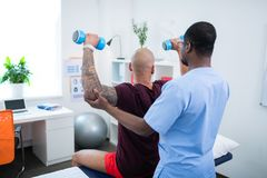 Therapist helping his patient doing exercises with barbells. Therapist helping. Dark-skinned therapist helping his patient with tattoos doing exercises with stock image