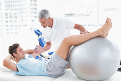 Therapist helping his patient with exercise ball. In medical office Stock Photo