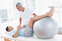 Therapist helping his patient with exercise ball. In medical office Stock Photography