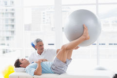 Therapist helping his patient with exercise ball. In medical office Royalty Free Stock Photo