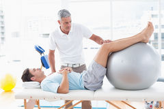 Therapist helping his patient with exercise ball. In medical office Royalty Free Stock Photography