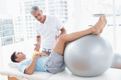 Therapist helping his patient with exercise ball. In medical office Royalty Free Stock Photos