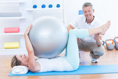 Therapist helping his patient with exercise ball Royalty Free Stock Photography