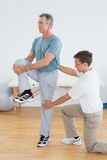 Therapist helping man with stretching exercises in gym hospital Royalty Free Stock Image