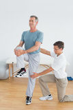 Therapist helping man with stretching exercises in gym hospital Royalty Free Stock Photos