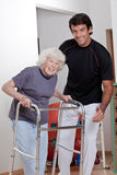 Therapist helping Patient use Walker. A therapist assisting a senior women onto her walker Stock Photo