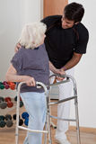 Therapist helping Patient use Walker. A therapist assisting a senior women onto her walker Stock Photography