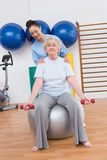 Therapist helping senior woman fit dumbbells on exercise ball Royalty Free Stock Photography