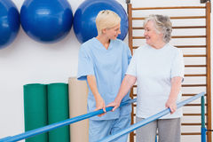 Therapist helping senior woman to walk with parallel bars Royalty Free Stock Photo