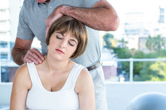 Therapist holding head of pregnant woman while massaging Royalty Free Stock Image