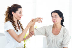 Therapist holding her patients arm Stock Image