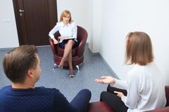 Therapist listening her patients and taking notes Royalty Free Stock Images