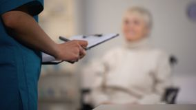 Therapist making notes in medical records and examining elderly lady, hospital