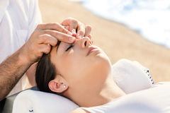 Therapist manipulating energetic points on female face outdoors. Close up of portrait of osteopath manipulating energetic points on female face outdoors Stock Images