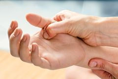 Therapist manipulating hand of female patient. Macro close up of kinesiologist applying pressure on hand of female patient Royalty Free Stock Photos