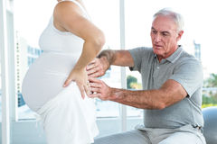 Therapist massaging back of pregnant woman Royalty Free Stock Photos