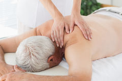 Therapist massaging back of senior man. Female massage therapist massaging back of senior man in medical office Royalty Free Stock Photo