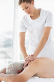 Therapist massaging back of senior man. Female massage therapist massaging back of senior men in clinic Royalty Free Stock Images