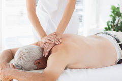 Therapist massaging back of senior patient Royalty Free Stock Images