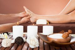 Therapist massaging customer's foot at beauty spa Royalty Free Stock Photos
