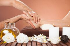Therapist massaging customer's foot at beauty spa Royalty Free Stock Photo
