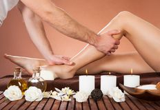 Therapist massaging customer's leg at beauty spa Stock Photo