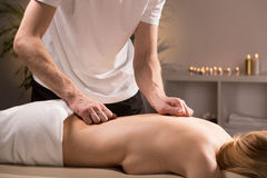 Therapist massaging female back Stock Image