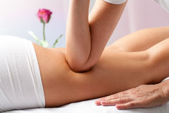 Therapist massaging female thigh with elbow. Royalty Free Stock Photography
