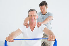 Therapist massaging a happy mans shoulder in gym hospital Stock Image