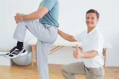 Therapist massaging mans lower back while gesturing thumbs up Royalty Free Stock Photos