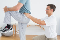 Therapist massaging mans lower back in gym hospital Stock Images
