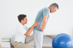 Therapist massaging mans lower back in gym hospital. Side view of a male therapist massaging mans lower back in the gym at hospital Stock Photography