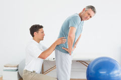 Therapist massaging mans lower back in gym hospital. Side view of a male therapist massaging mans lower back in the gym at hospital Stock Images