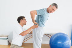 Therapist massaging mans lower back in gym hospital Royalty Free Stock Photos