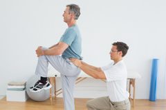 Therapist massaging mans lower back in gym hospital. Side view of a male therapist massaging mans lower back in the gym at hospital Stock Photo