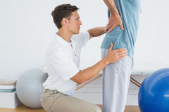 Therapist massaging mans lower back at hospital gym Royalty Free Stock Images