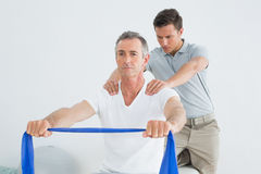 Therapist massaging mans shoulder in gym hospital Royalty Free Stock Photos