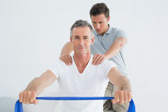 Therapist massaging mans shoulder in gym hospital Stock Photo