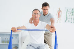 Therapist massaging mans shoulder in hospital Royalty Free Stock Photo