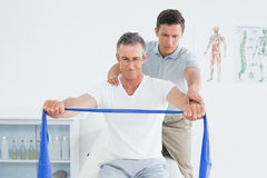 Therapist massaging mans shoulder in hospital Stock Image