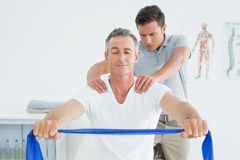 Therapist massaging mans shoulder in hospital Royalty Free Stock Photos